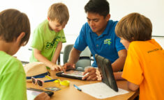 counselor showing three boys video games on an ipad