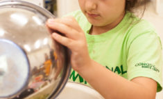 young girl tossing salad dressing into a bowl of salad