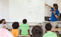 teacher holding a drone and showing information on a whiteboard to a room full of kids