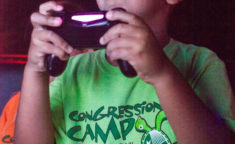 a young boy with a huge smile playing with a playstation controller