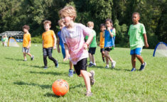 a boy kicking a soccer ball with a group of kids behind him