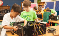 two young boys working on repairing a computer