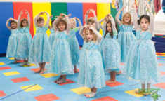a group of young girl campers dressed as elsa from frozen practicing dancing