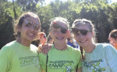 three girls smiling at the camera with all their sunglasses awkwardly at an angle