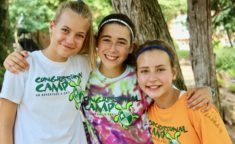 three girls with congressional camp shirt smiling at the camera