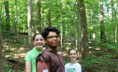 three campers in the woods smiling