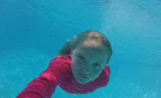 young girl smiling at camera while underwater