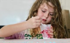 young girl scooping ice cream out of a cup