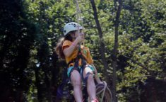 a young girl zip lining while holding rope