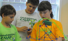 three campers working to construct a roller coaster project