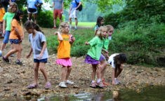 young girl campers playing by a stream of water