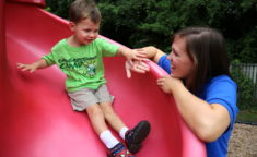 young child sliding down slide with camp counselor watching him
