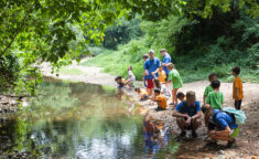 group of campers learning how to fish