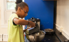 girl baking in kitchen at camp