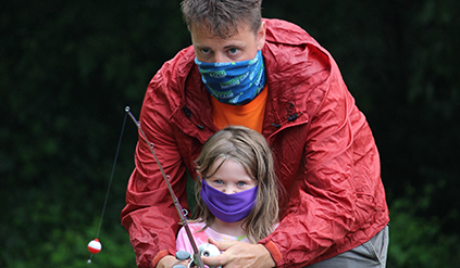 A counselor helping a camper fish