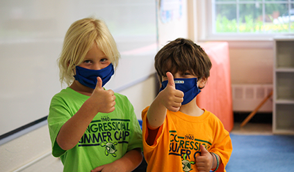 Two campers in mask giving a thumbs up.