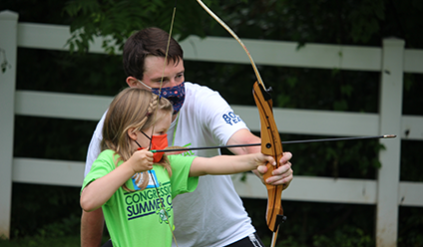 A counselor helping a camper with her archery skills