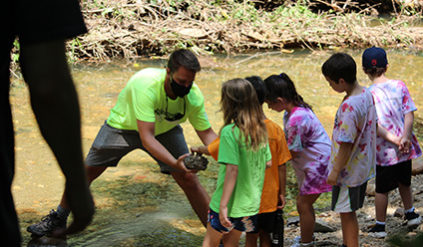 A counselor sharing a rock from the water with a group of campers.