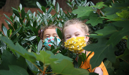 Two campers with masks on hiding in a bush