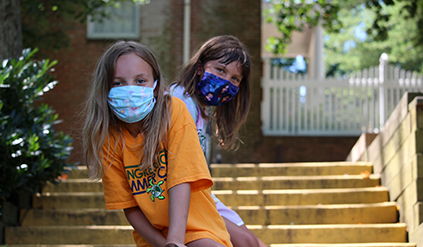 Two girls in masks sitting on a railing